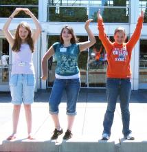 Three precollege participants spelling out OSU with their hands