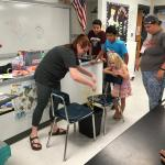 Students test their spaghetti bridge