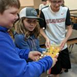 Students test their spaghetti bridge