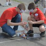 Students fuel their chemical-powered car.